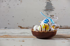 Huevos de Pascua hechos a mano coloridos dentro de un cuenco de madera Imagen de archivo