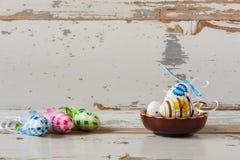 Huevos de Pascua hechos a mano pintados dentro de un cuenco de madera Fotografía de archivo libre de regalías