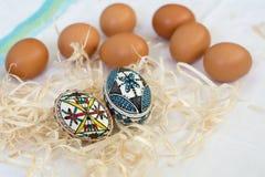 Huevos de Pascua hechos a mano tradicionales en paja en el paño blanco Imagen de archivo libre de regalías