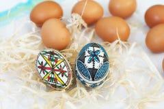 Huevos de Pascua hechos a mano tradicionales en paja en el paño blanco Foto de archivo libre de regalías