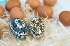 Huevos de Pascua hechos a mano tradicionales en paja en el paño y el FE blancos Fotografía de archivo libre de regalías