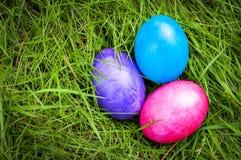 Huevos de Pascua hundidos profundamente en hierba verde Imagen de archivo libre de regalías