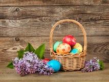Huevos de Pascua de la lila y del oro en una cesta en un viejo tablero Fotografía de archivo libre de regalías