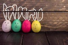 Huevos de Pascua lindos divertidos en fondo de madera rústico Fotos de archivo