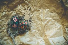 Huevos de Pascua de madera coloridos y conejo de madera del trasero en un fondo del papel del arte entonado imagenes de archivo