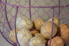 Huevos de Pascua manchados en una cesta de alambre Fotos de archivo