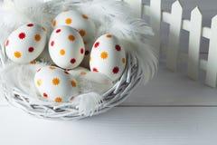 Huevos de Pascua modelados en la cesta Fotos de archivo