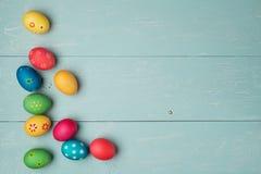 Huevos de Pascua multicolores en fondo de madera del vintage Fotos de archivo libres de regalías