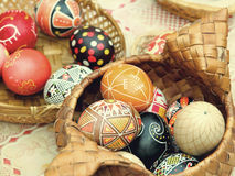 Huevos de Pascua multicolores en pote de la paja Fotos de archivo