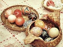 Huevos de Pascua multicolores en potes de la paja en una tabla Imagen entonada Foto de archivo libre de regalías