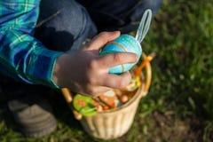 Huevos de Pascua multicolores en una mano del ` s del niño y en una cesta de mimbre foto de archivo libre de regalías