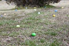 Huevos de Pascua multicolores que ponen en un campo de la hierba Imagenes de archivo