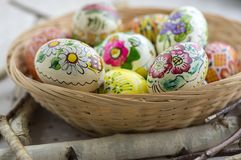 Huevos de Pascua pintados coloridos en la cesta de mimbre marrón en ramas, vida tradicional de Pascua aún, flores pintadas, jerar Foto de archivo