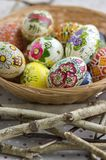 Huevos de Pascua pintados coloridos en la cesta de mimbre marrón en ramas, vida tradicional de Pascua aún, flores pintadas, jerar Fotografía de archivo