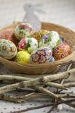 Huevos de Pascua pintados coloridos en la cesta de mimbre marrón en ramas, vida tradicional de Pascua aún, flores pintadas, jerar Foto de archivo libre de regalías