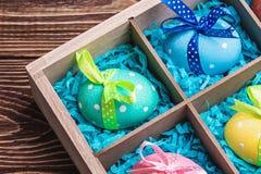 Huevos de Pascua pintados coloridos en una caja de madera Imagen de archivo