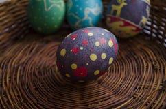 Huevos de Pascua pintados coloridos en una cesta tejida de la paja Imagen de archivo