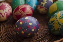 Huevos de Pascua pintados coloridos en una cesta tejida de la paja Imágenes de archivo libres de regalías