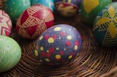 Huevos de Pascua pintados coloridos en una cesta tejida de la paja Fotografía de archivo libre de regalías