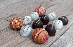 Huevos de Pascua pintados coloridos hechos a mano con los caramelos de chocolate contra fondo de madera Foto de archivo libre de regalías