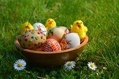 Huevos de Pascua pintados coloridos y pequeñas ovejas en una hierba verde Fotos de archivo libres de regalías