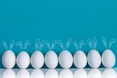 Huevos de Pascua pintados con los oídos de conejos y los ballooons en el fondo azul Foto de archivo