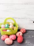 Huevos de Pascua pintados en cesta verde adornada en la tabla de madera Fotos de archivo