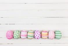 Huevos de Pascua pintados en colores en colores pastel en una madera blanca Fotografía de archivo