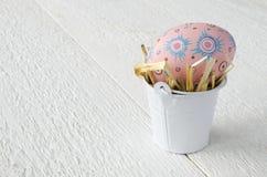 Huevos de Pascua pintados en un cubo en una tabla de madera blanca, texto co imágenes de archivo libres de regalías