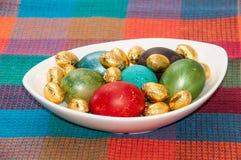 Huevos de Pascua pintados en un cuenco blanco en el mantel de la cocina fotos de archivo