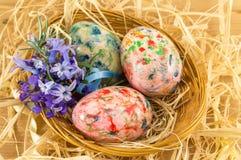 Huevos de Pascua pintados en una jerarquía de la paja Foto de archivo