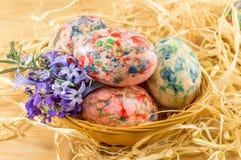 Huevos de Pascua pintados en una jerarquía de la paja Fotos de archivo