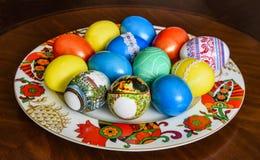 Huevos de Pascua pintados y pintados en azul, rojo, amarillo coloreado en una placa hermosa imágenes de archivo libres de regalías