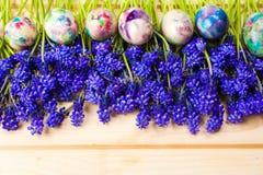 Huevos de Pascua pintados y flores púrpuras de la primavera Imagen de archivo libre de regalías