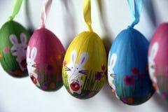 Huevos de Pascua plásticos jadeados coloridos con los conejitos blancos en fila Imagen de archivo