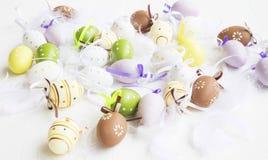 Huevos de Pascua punteados, pintado, adornado con las plumas en los vagos blancos Imagen de archivo