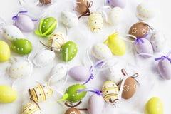 Huevos de Pascua punteados, pintado, adornado con las plumas en los vagos blancos Foto de archivo libre de regalías
