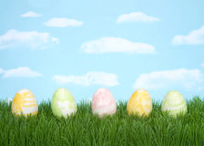 Huevos de Pascua remolinados en colores pastel en fondo del cielo de la hierba Fotos de archivo