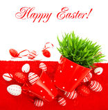Huevos de Pascua rojos con la hierba verde sobre la cubierta de tabla Imagen de archivo