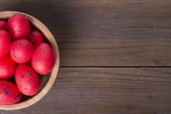 Huevos de Pascua rojos en el cuenco de madera Imagen de archivo libre de regalías
