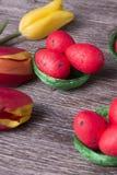 Huevos de Pascua rojos en jerarquía verde y tulipanes coloridos Fotografía de archivo libre de regalías