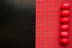 Huevos de Pascua rojos, en un fondo de madera negro El concepto de a Imagenes de archivo