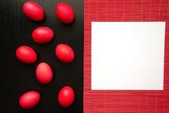 Huevos de Pascua rojos, en un fondo de madera negro El concepto de a Fotografía de archivo libre de regalías