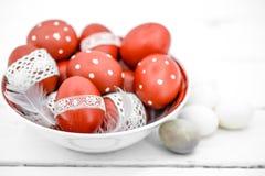 Huevos de Pascua rojos en una placa blanca Fotos de archivo