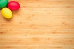 Huevos de Pascua rojos, verdes, amarillos en un fondo de madera ligero Huevo Foto de archivo libre de regalías