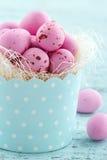 Huevos de Pascua rosados en una taza de la magdalena Imagenes de archivo