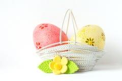 Huevos de Pascua rosados y amarillos en una cesta con la flor amarilla Imagenes de archivo
