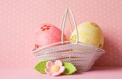 Huevos de Pascua rosados y amarillos en una cesta con la flor rosada Imágenes de archivo libres de regalías