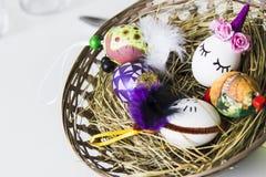 Huevos de Pascua sobre cesta de mimbre con el heno Imágenes de archivo libres de regalías