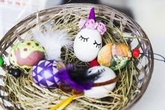 Huevos de Pascua sobre cesta de mimbre con el heno Foto de archivo